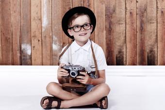 Hipster boy on floor holding camera