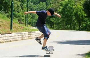 Skateboarding boy in jean shorts and a tee