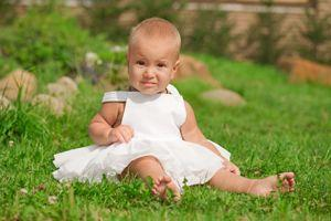 Baby girl in white dress on grass