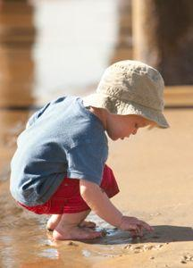 toddler in red shorts at beach