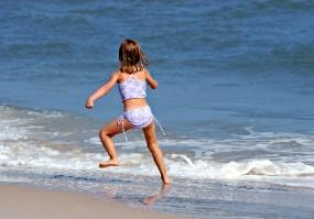 Young girl in a swimsuit running along the beach
