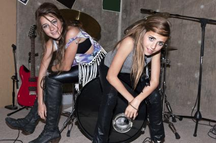 Glam grunge girls sitting on drums