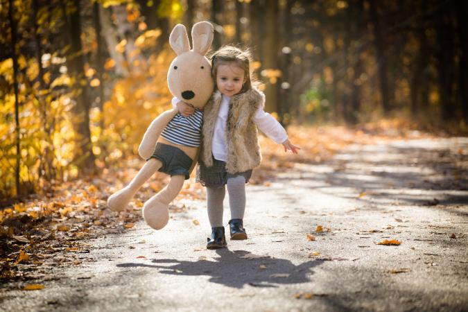 Toddler girl in fur vest running