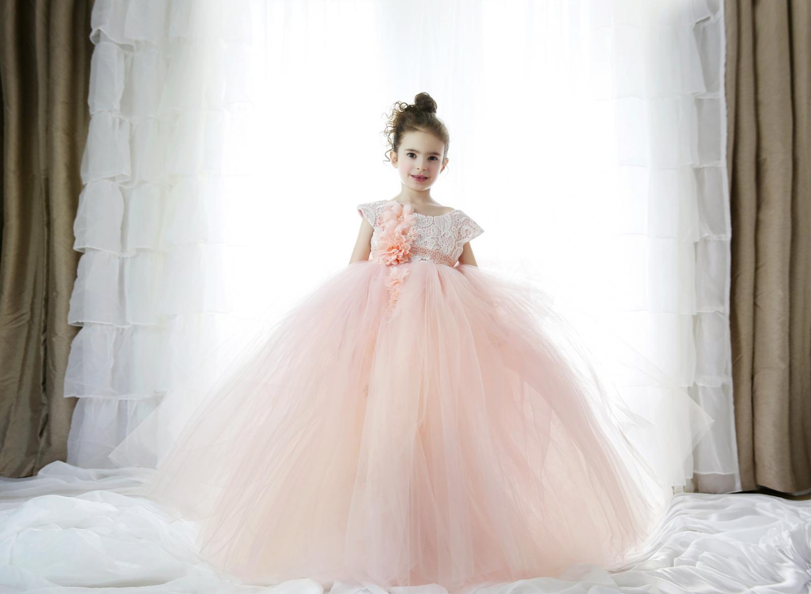 Beautiful little girl wearing a princess gown and standing in front of large window