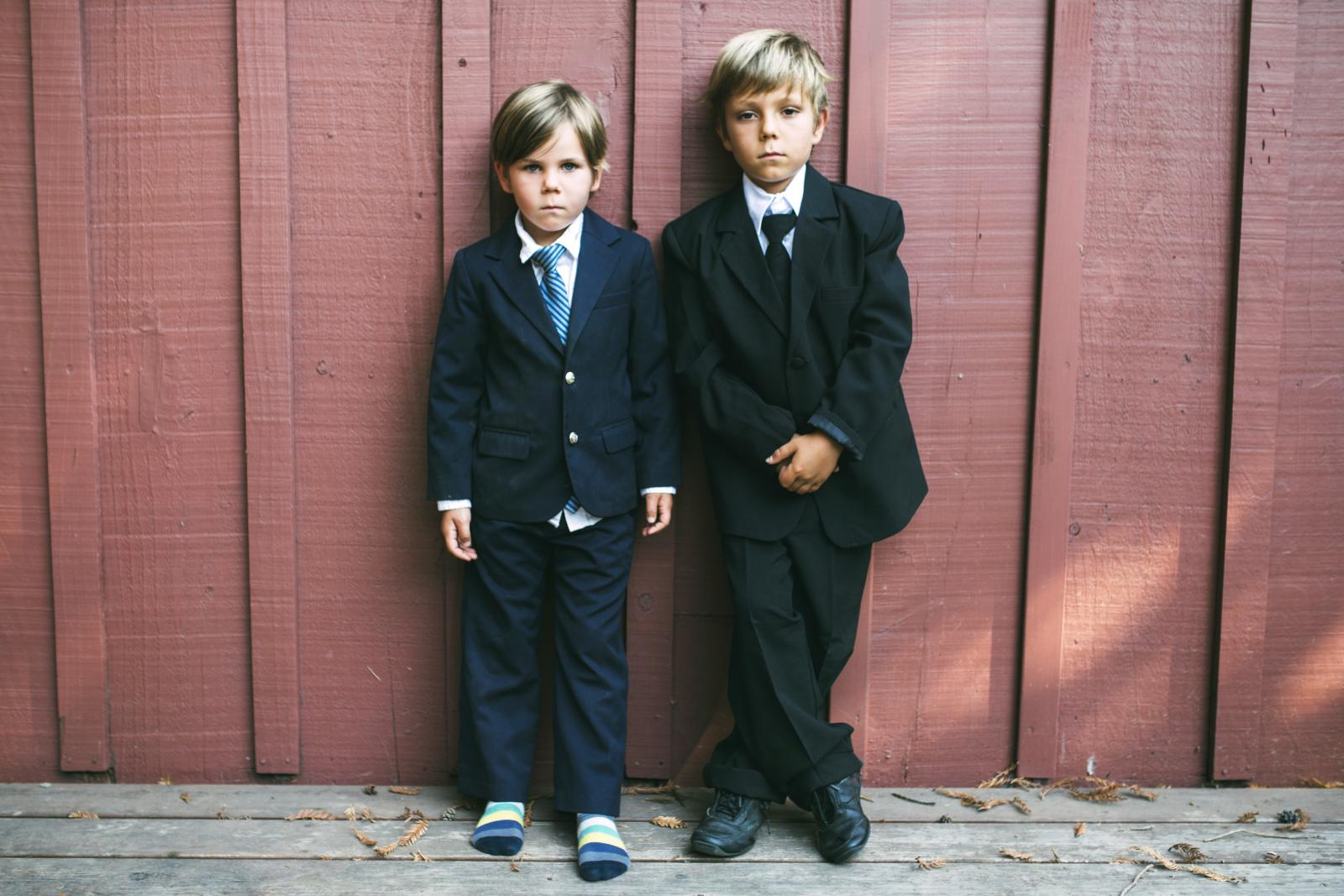 Brothers wearing suits while standing against wooden wall