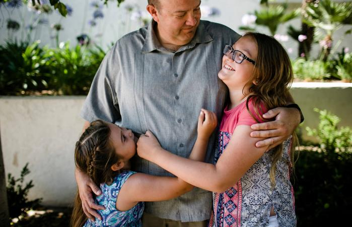 Happy daughters embracing father