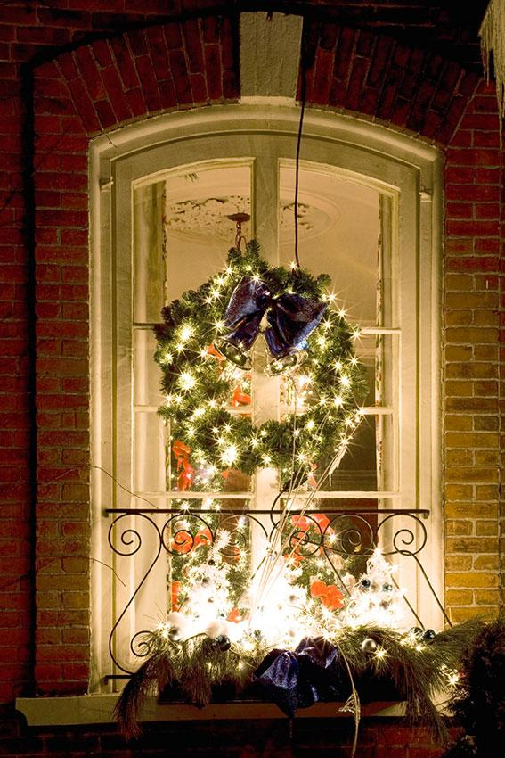 decorated red christmas bauble source wreath with lights in window
