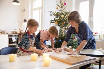 Modern mother making cookies with daughter and son at christmas