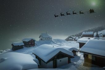 Santa's sledge in a starry sky over a village in the snow