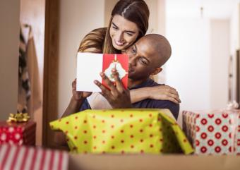 Woman embracing boyfriend while reading card