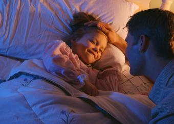 Father talking to daughter and tucking her into bed