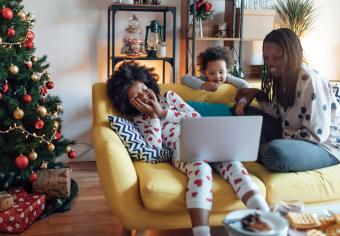 Mother and daughters watching Santa on laptop