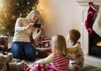 Mother taking photo of kids on Christmas morning