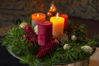 Candles With Pine Cones And Wreath On Table