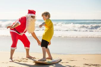 Australian summer Santa Claus showing young boy how to surf