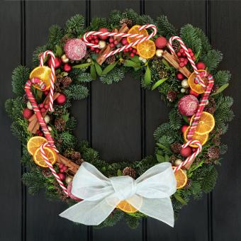 Christmas wreath on door with candy canes and fruit