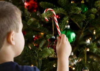Boy decoranting christmas tree with candy cane