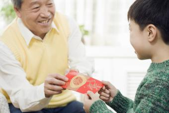 Chinese grandfather giving grandson red pocket