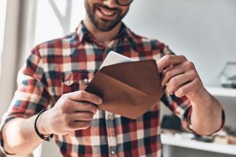 Young man opening envelope