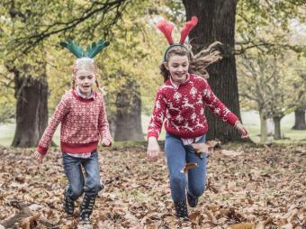 Two girls running while wearing reindeer antlers