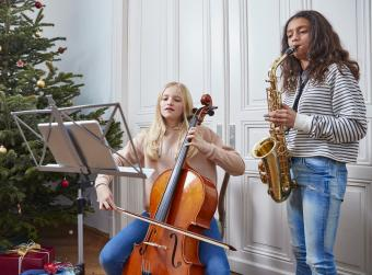 Two girls playing cello and saxophone at Christmas