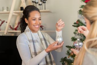 Friends hanging ornaments on Christmas tree together