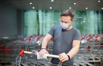Man wipes shopping cart handle