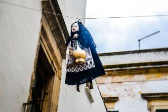 Typical Epiphany scene in Italy with a Befana hanging on a cable