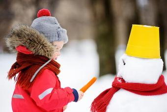 Little boy having fun with snowman.