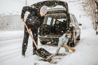 Father and son cleaning snow around car