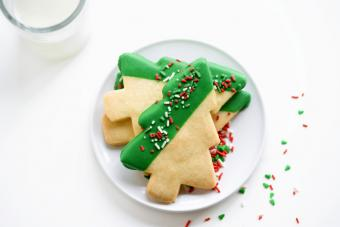 Shortbread Christmas tree cookies on white plate with glass of milk
