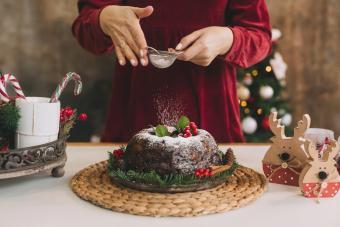 Woman Dusting Powder Sugar On Cake