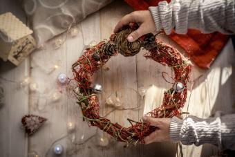 Kid hold up a decorative christmas wreath