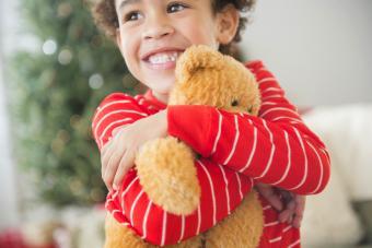 Girl hugging teddy bear at Christmas