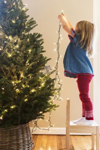 Girl hanging lights on Christmas tree