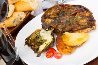Lamb head with artichoke, tomatoes and potatoes