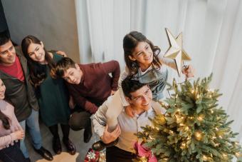 girl putting star on christmas tree