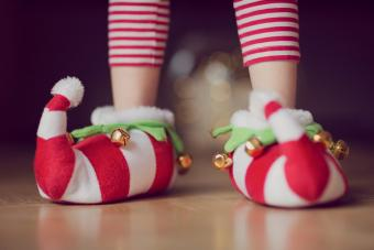 Child wearing Christmas slippers with bells