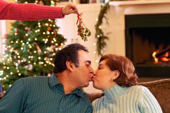 Woman dangling mistletoe in between kissing couple