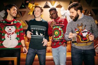 Cheerful Friends Having Fun In Nightclub Wearing Christmas Sweaters