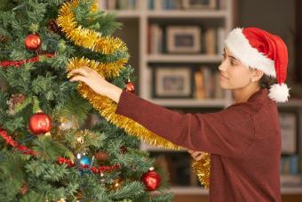 Woman adding garland on Christmas tree