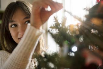 Woman placing tinsel on Christmas tree