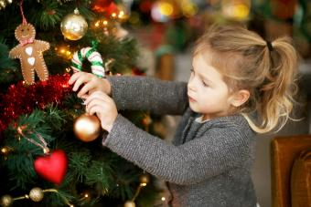 Little girl holding a Christmas tree bauble