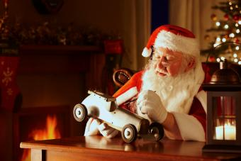 Santa painting a toy car in his workshop