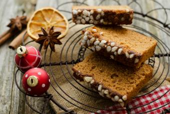 Gingerbread cake with christmas baubles and dried orange, spice on wooden table,