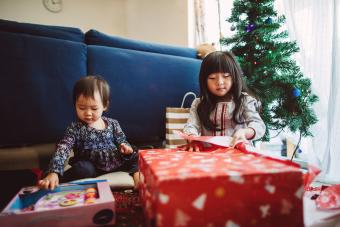 lovely little girl opening Christmas presents with her little baby sister at home