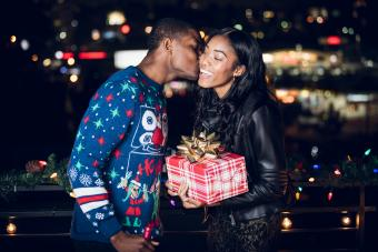 Young man giving girlfriend Christmas present