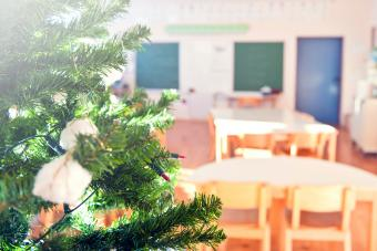 Christmas tree in school classroom, traditional wooden desks and chairs and blackboard