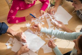Classmates cutting out paper snowflakes with teacher