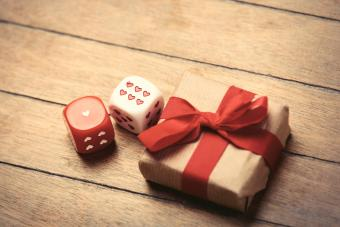 Beautiful gift and small dice on the wonderful brown wooden background
